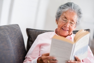 Elder woman reading a book at home and smiling